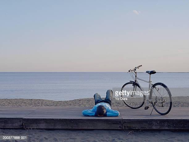 Man lying on boardwalk with bicycle near beach