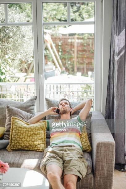 Man lying on couch using cell phone