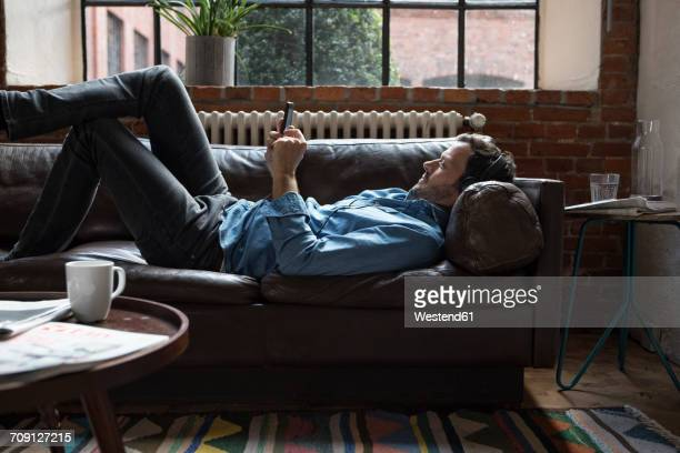 man lying on couch, using smart phone - sofa stock-fotos und bilder