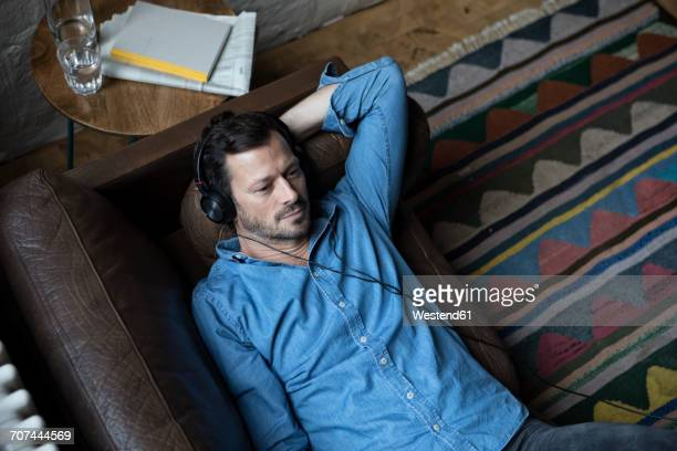 man lying on couch, wearing head phones - solo adulti foto e immagini stock