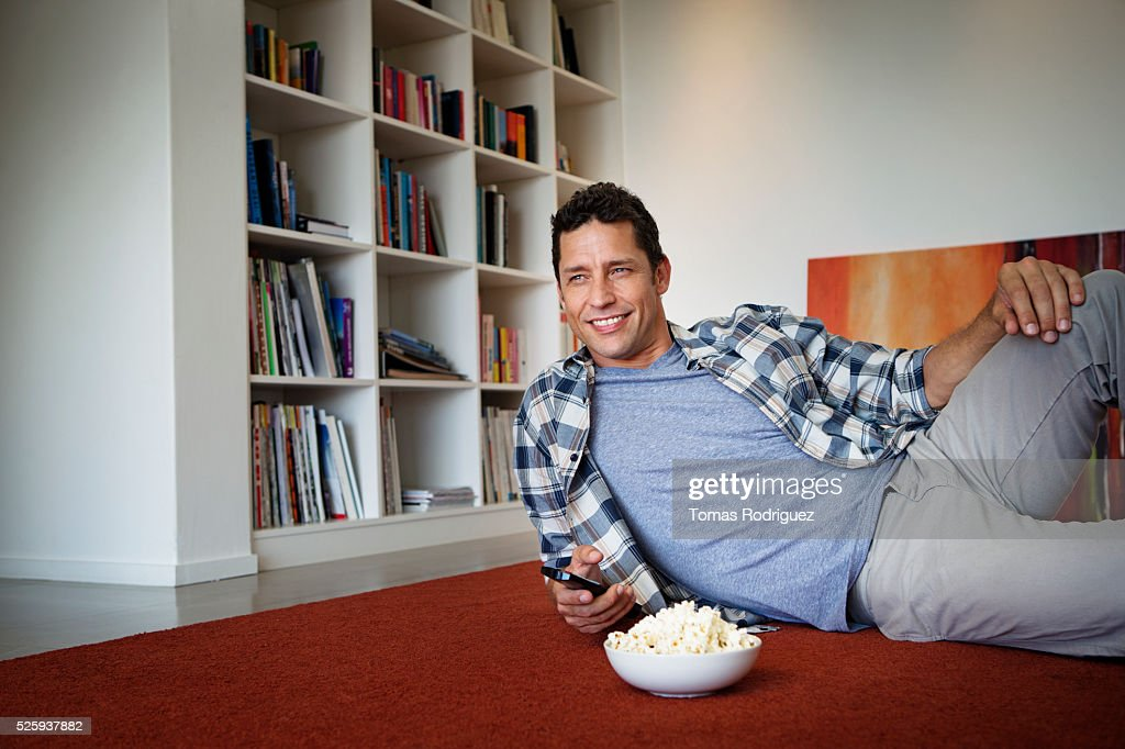 Man lying on floor and watching tv : Stock Photo