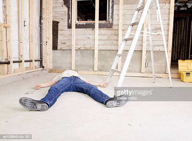 Man lying on floor beside stepladder on construction site