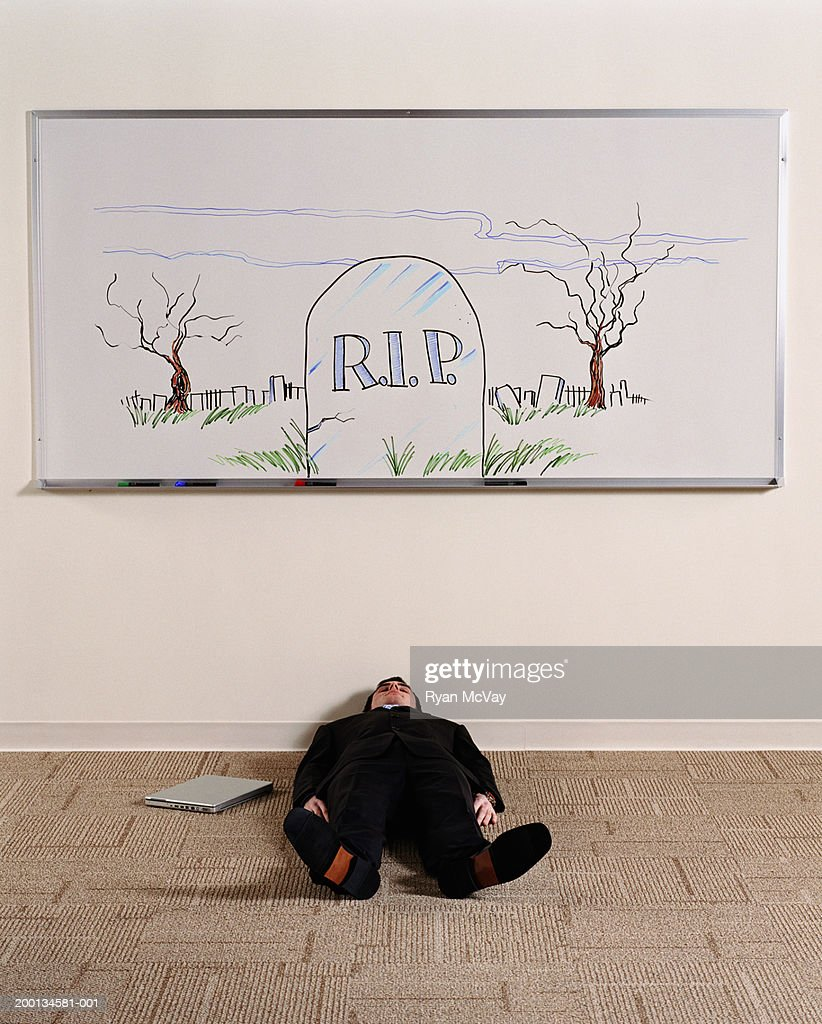 Man lying on floor under whiteboard illustrated with grave stone : Stock Photo