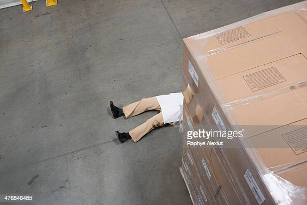 Man lying on floor with cardboard boxes in warehouse