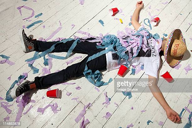 Man lying on floorboard covered with streamers at party