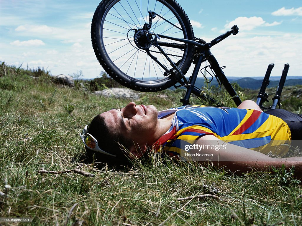 Man lying on grass beside mountain bicycle, side view : Stock Photo