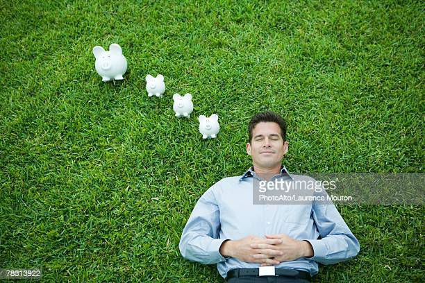 Man lying on grass, line of piggy banks by head