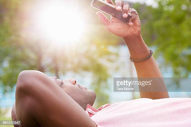 man lying on grass looking at mobile