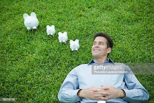man lying on grass, next to piggy banks, smiling - só um homem maduro imagens e fotografias de stock
