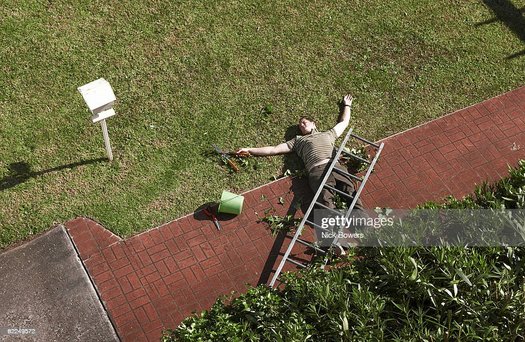 Man lying on ground with ladder on top of him : Stock Photo