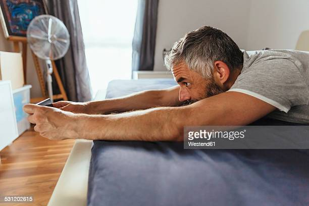 Man lying on his bed taking a selfie with his smartphone