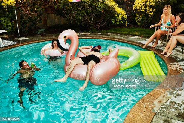 Man lying on inflatable pool toy while hanging out with friends during backyard pool party on summer evening