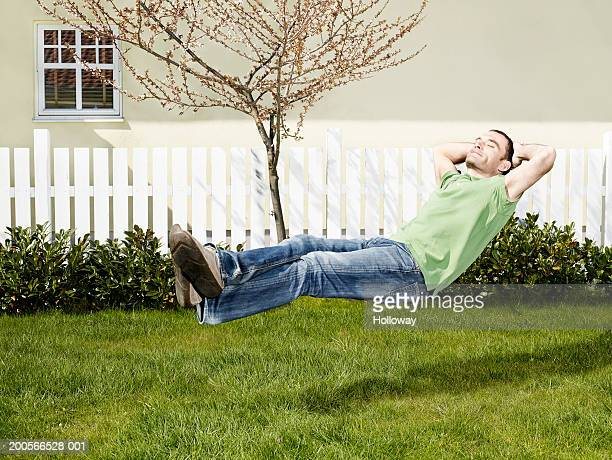 Man lying on invisible chair in garden (digital composite)