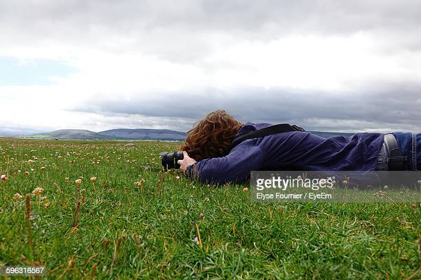 Man Lying On Landscape And Photographing