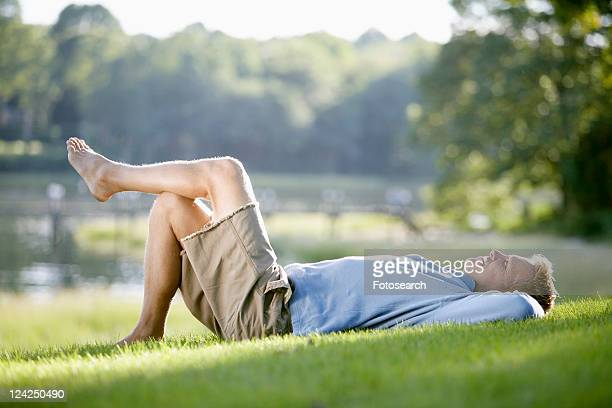 man lying on lawn - legs behind head stock pictures, royalty-free photos & images
