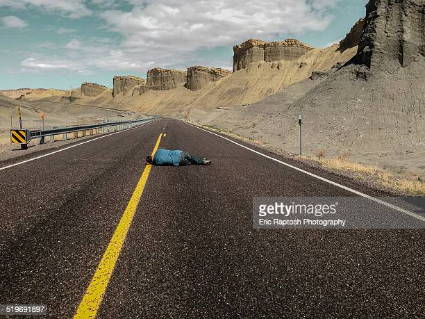 Man lying on lonely scenic highway mid line