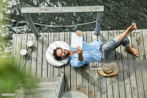 Man lying on platform at the waterside holding digital tablet
