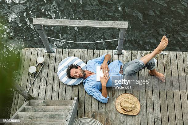 man lying on platform at the waterside - houseboat stock pictures, royalty-free photos & images