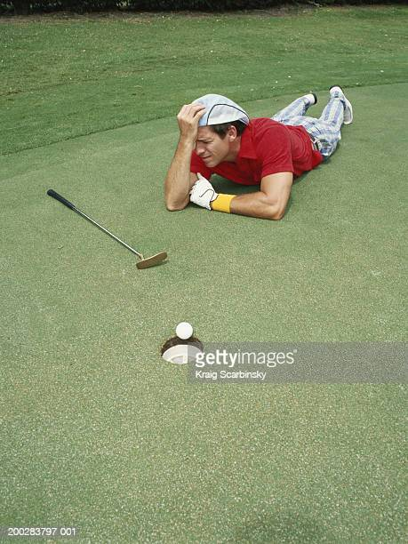 man lying on putting green beside golf ball at edge of hole, head in hands - golf humour photos et images de collection