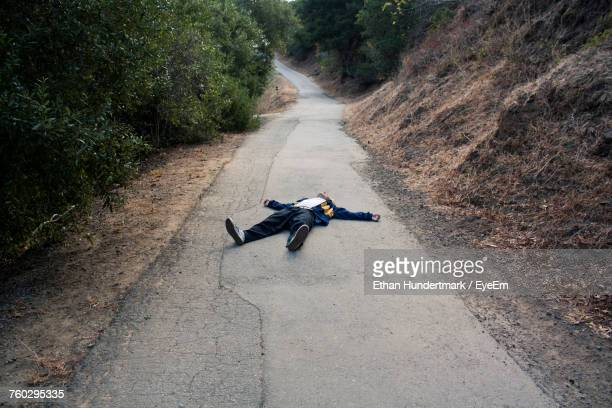 man lying on road - lying down foto e immagini stock