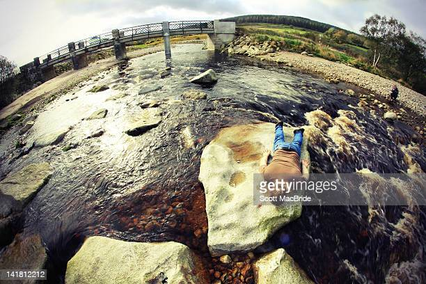 man lying on rock - scott macbride stock pictures, royalty-free photos & images
