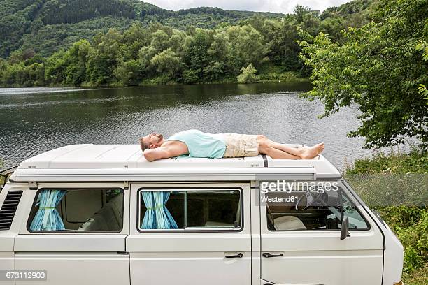 Man lying on roof of a van at lakeside