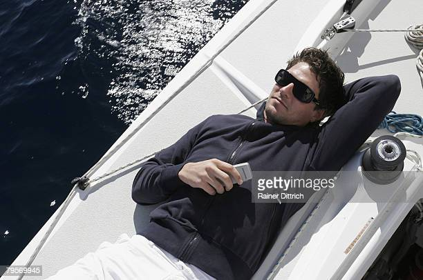 Man lying on sailing boat holding mobile phone, elevated view