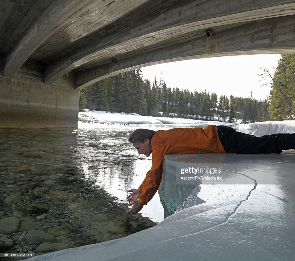 Man lying on snowy riverbank, scooping for water under bridge, side view : Stockfoto