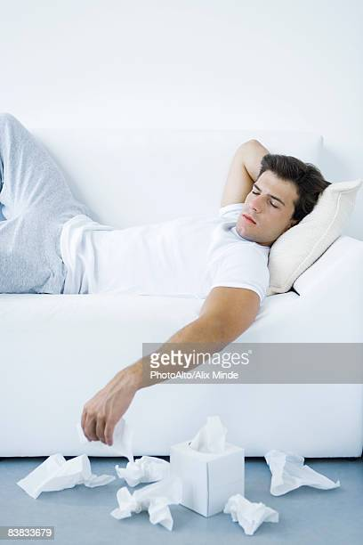 Man lying on sofa, discarded tissues on the floor beside him