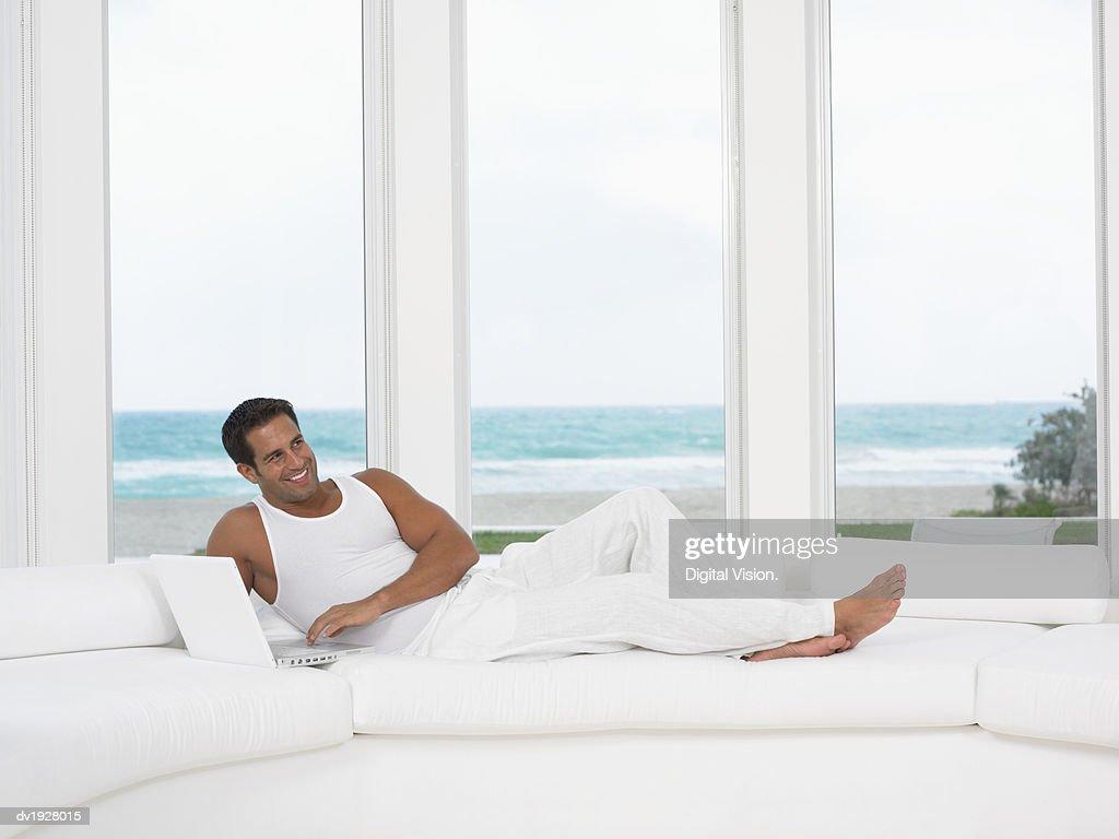 Man Lying on Sofa in His Pajamas Using His Laptop : Stock Photo