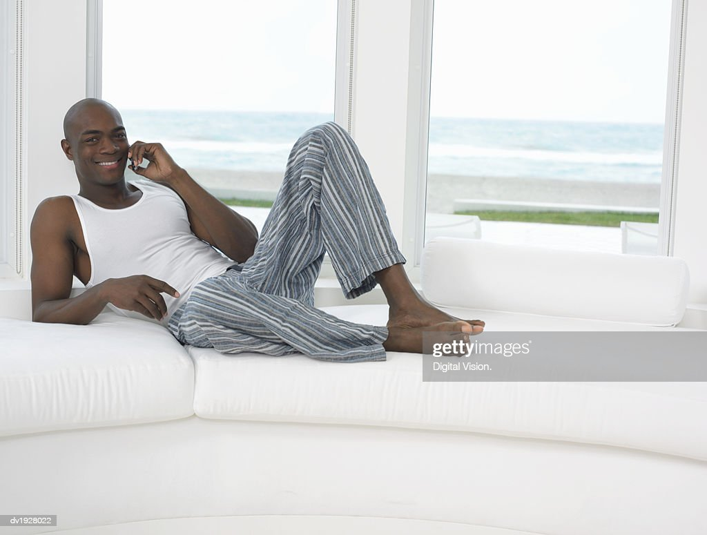 Man Lying on Sofa in His Pyjamas Using a Mobile Phone : Stock Photo