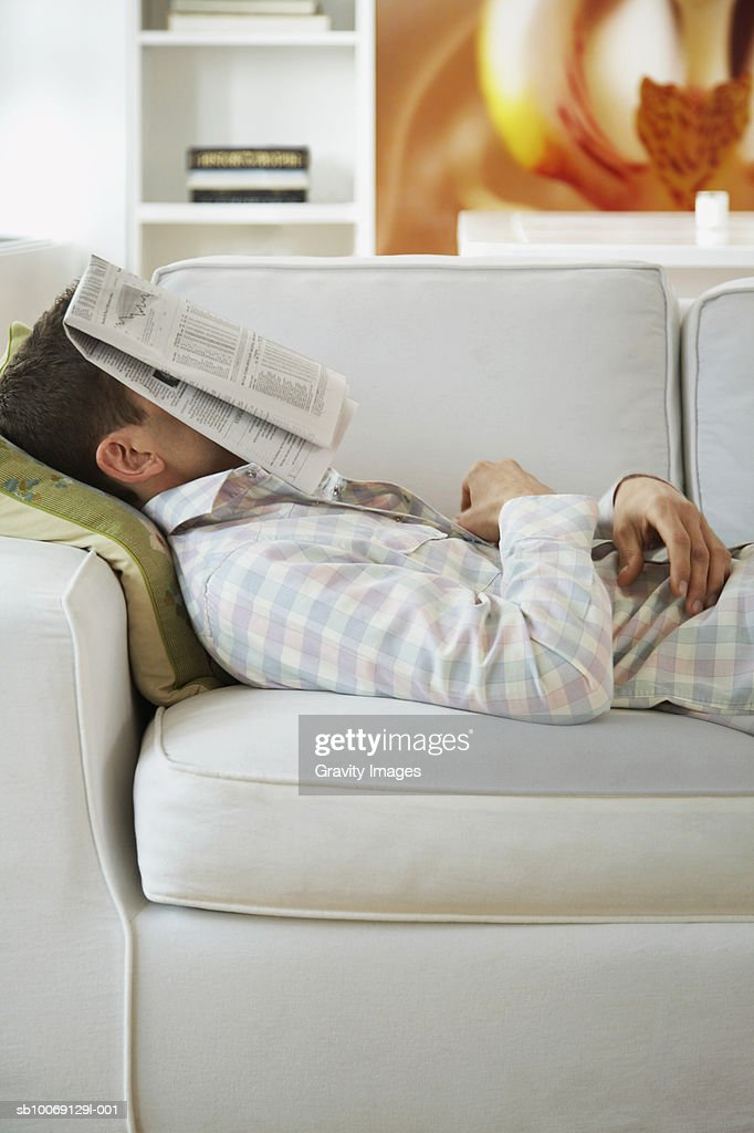 Man lying on sofa with newspaper on face, side view : Stockfoto