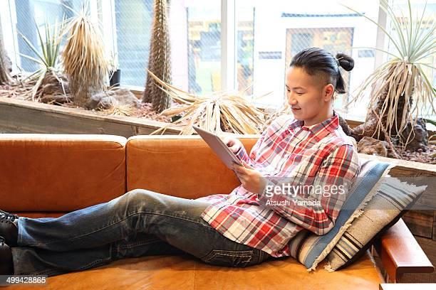 Man lying on sofa,using digital tablet