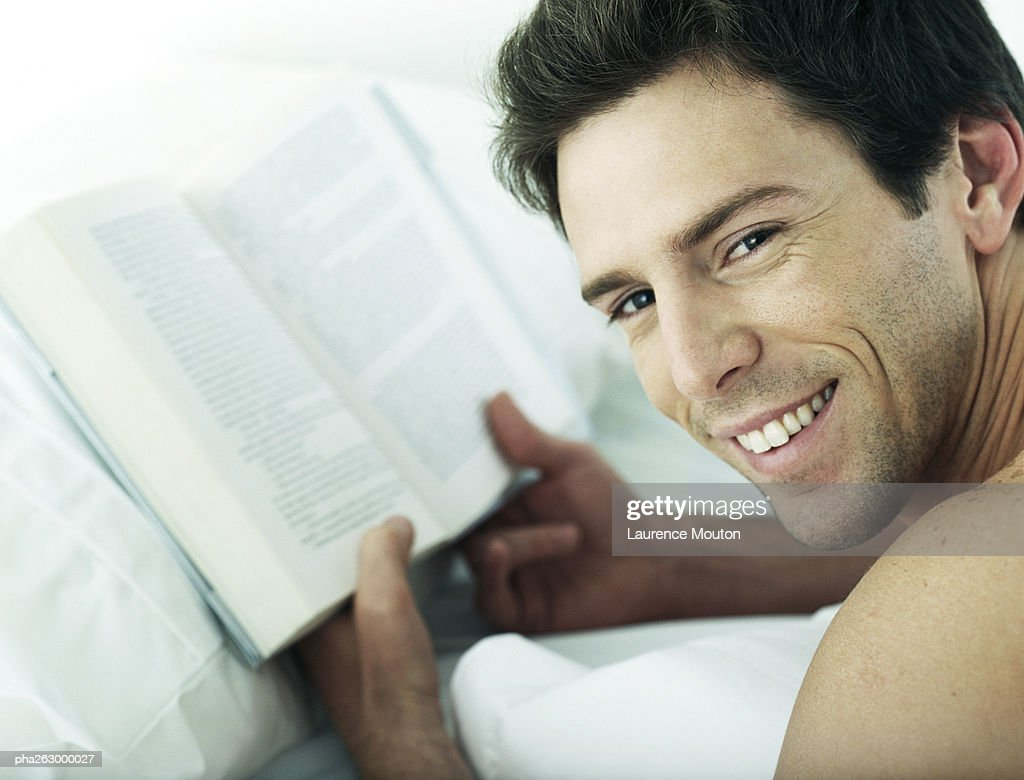Man lying on stomach holding book, looking over shoulder at camera, close-up : Stockfoto