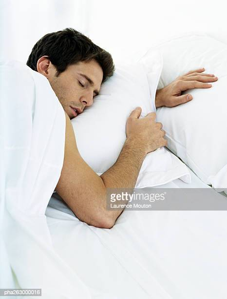 Man lying on stomach on bed with eyes closed