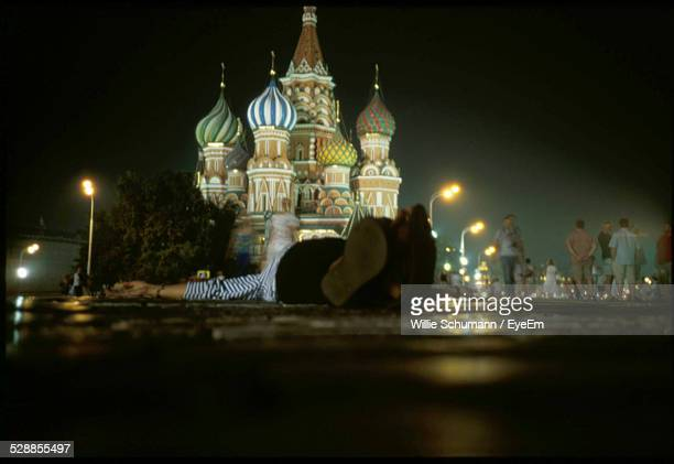 man lying on street in front of saint basils cathedral - national drunk stock photos and pictures