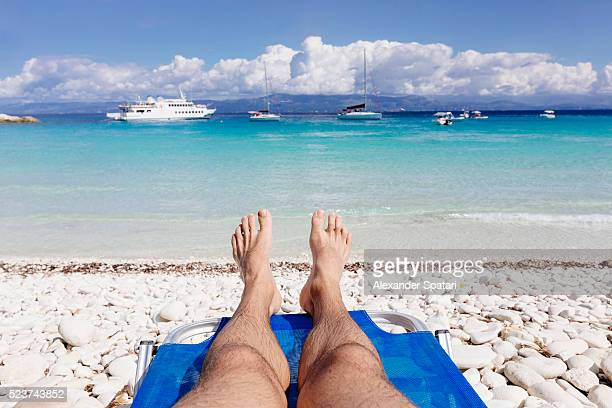 Man lying on sunbed on the beach in Greece, low section, personal perspective view