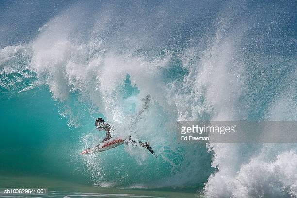 Man lying on surfboard in sea