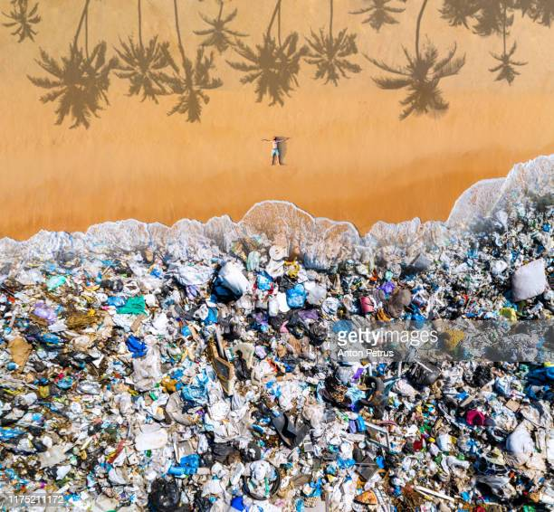 man lying on the beach with garbage in the water. ocean pollution concept with plastic and garbage - plastic stockfoto's en -beelden