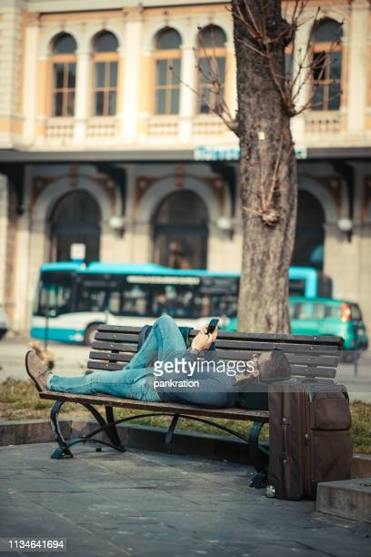 man lying on the bench and texting - station stock pictures, royalty-free photos & images