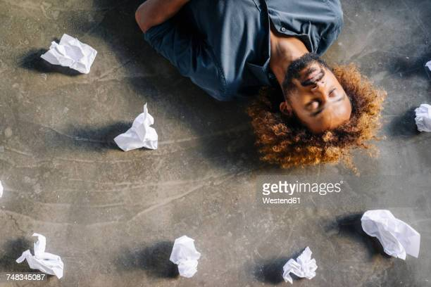 Man lying on the floor surrounded by crumpled paper