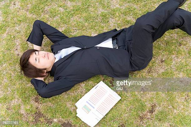 Man lying on the lawn, closing eyes, high angle view, Japan