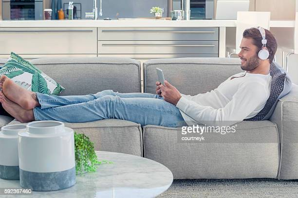 man lying on the sofa with headphones. - beau pied homme photos et images de collection