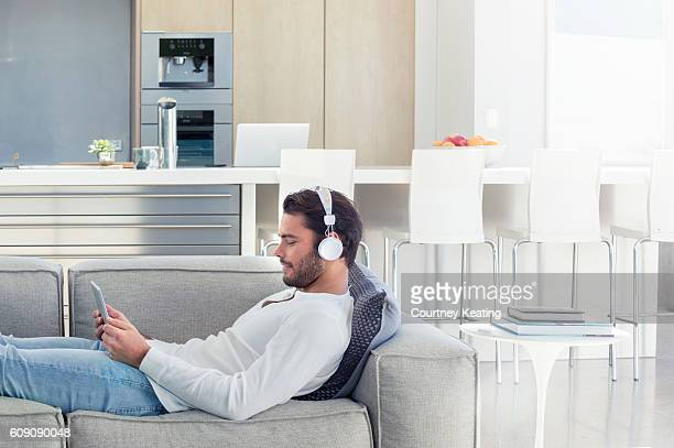 Man lying on the sofa with headphones.