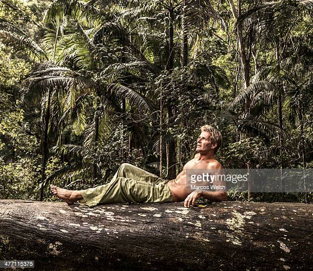 Man lying on tree log in the forest