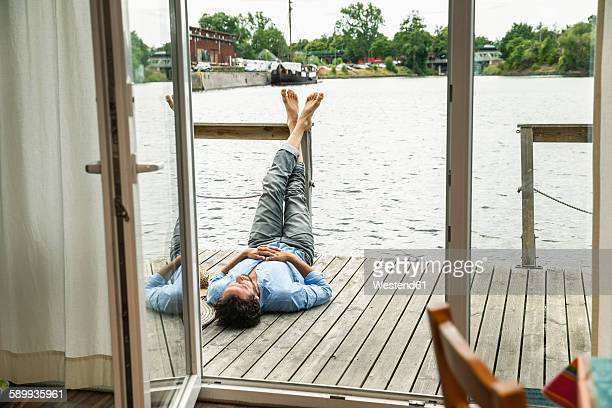 man lying on wooden deck of a house boat - houseboat stock pictures, royalty-free photos & images