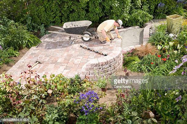 man lying paving stones in garden, elevated view - paving stone stock pictures, royalty-free photos & images