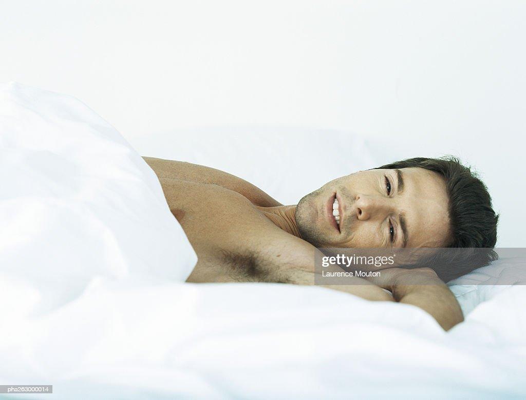Man lying shirtless on bed looking at camera : Stockfoto