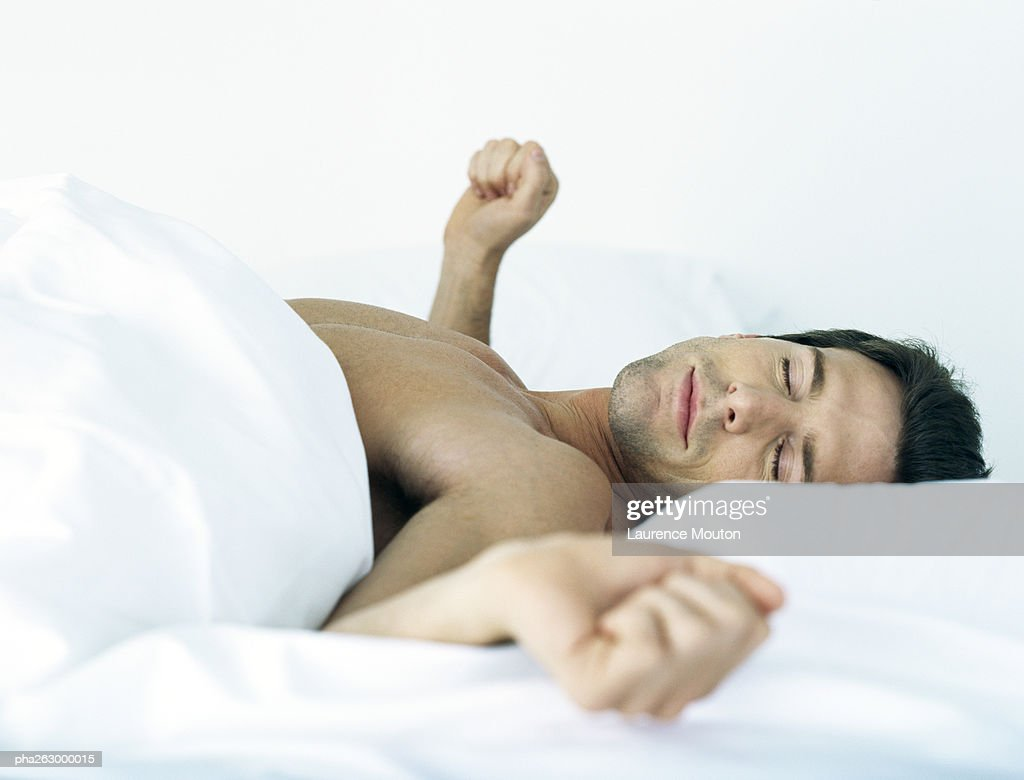 Man lying shirtless on bed, stretching arms to the side, eyes closed : Stockfoto
