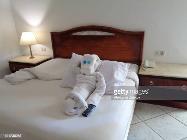 a man made or folded from a towel on a hotel bed, holding a tv remote in his hand. concept of tourist rest - art deco furniture stock pictures, royalty-free photos & images